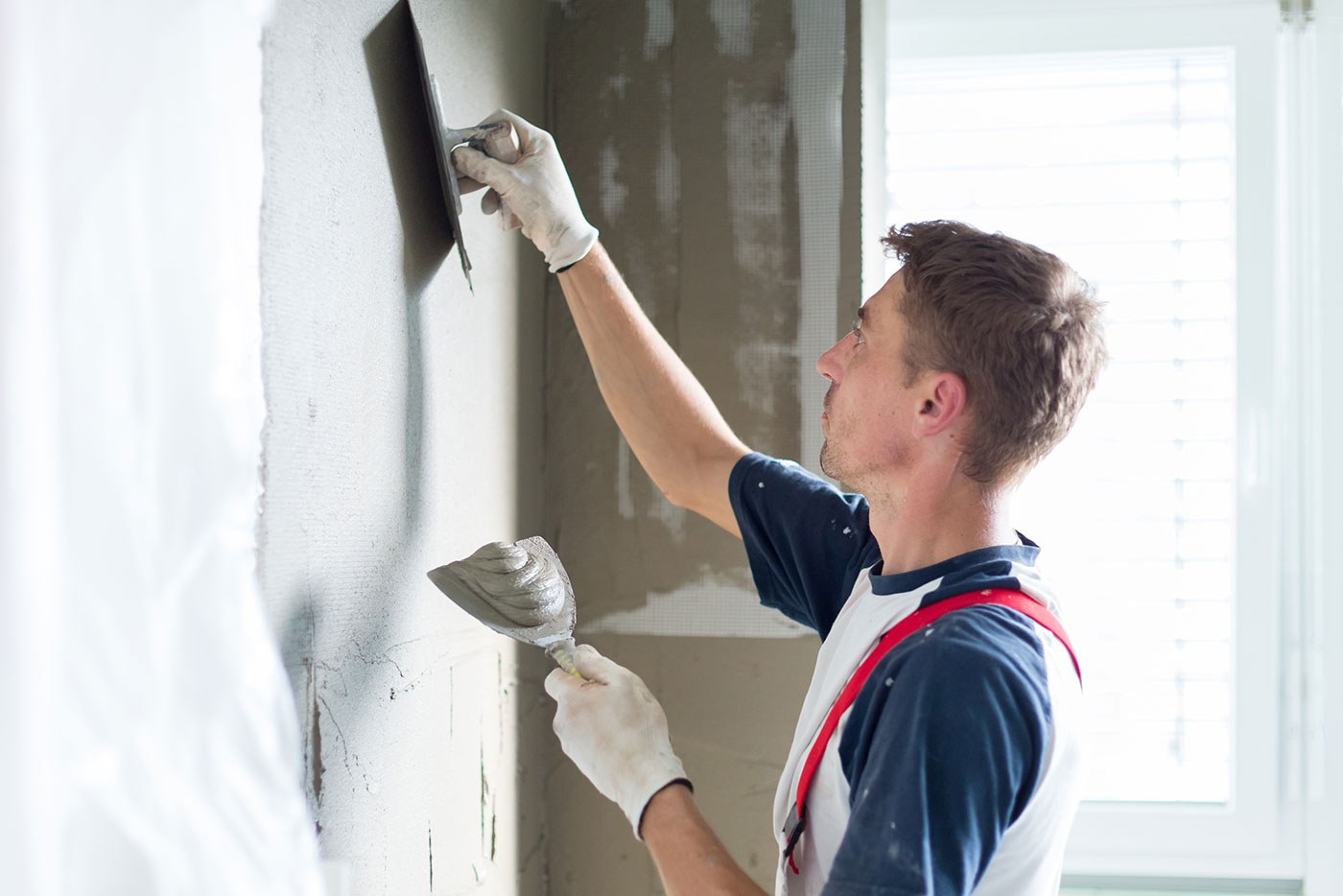 man spackling wall
