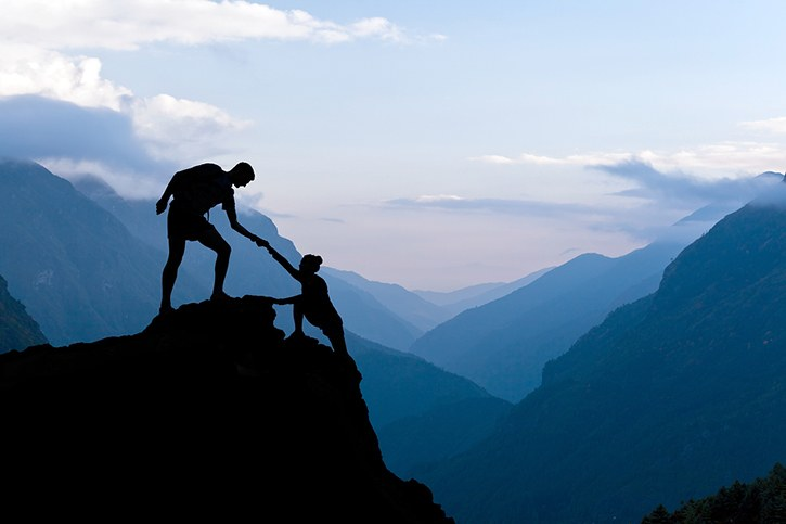 person helping another up a mountain top