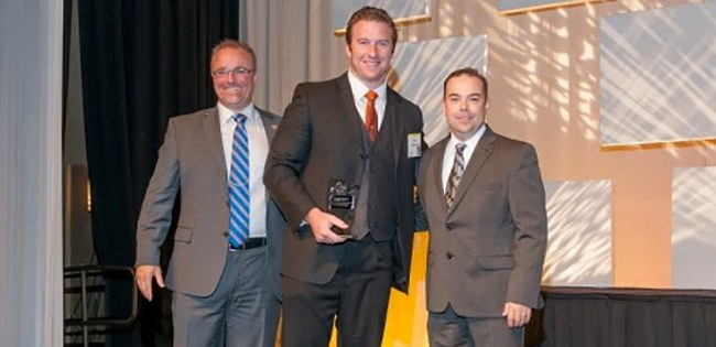"""Former Boise State University Football Captain and local businessman, Nick Schlekeway, has been named one of the state's """"Accomplished Under 40"""" by the Idaho Business Review. Selected from hundreds of nominees, the recipients at the 15th annual event were publicly recognized for their accomplishments and """"On the rise status"""" in the business community. """"'These young professionals are talented and have risen head and shoulders above others, already proving they are successful in their careers and continuing upward,' said Sean Evans, Vice President and Publisher for Idaho Business Review. 'These are the people shaping our state, our expectations and our future'."""" The Idaho Business Review's Accomplished Under 40 event was sponsored by Boise State University's College of Business and Economics. The Dean of the College of Business, Ken Petersen, was a guest speaker at the June 26th Event. """"It is important to point out that these members of our community aren't even middle age yet. To be accomplished at this age is quite remarkable. Given these recipients' steep professional trajectories; I hold great hope for their accomplishments over 40!"""" In Addition, Mr. Petersen, former client of Nick Schlekeway, specifically highlighted him as an example of the type of forward thinking & determined young professionals who would push the Boise, Idaho economy and business community to new heights of achievement. Mr. Schlekeway is the co-founder of the fastest-growing Residential and Commercial Real Estate Company in the State of Idaho, Amherst Madison. This accomplishment is no surprise to those who know him and have witnessed his previous successes at the highest levels of academics, sports, and public service. In 2007, Boise State University head coach, Chris Petersen, was quoted; """"Schlekeway is one of our top leaders. He leads by example every day. He shows up ready to go to work and is extremely intense. If the rest of the guys can become as intense as he is, we are going to win a"""